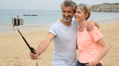Couple taking picture with smartphone and extendable monopod Stock Footage