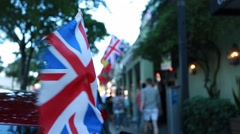 English Flag waving in a street with people passing by Stock Footage