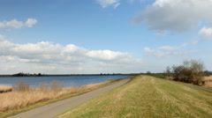 Lone bicyclist on dike in Holland. Stock Footage