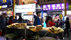 Stall with cooked pancakes against night pedestrian area lights and crowd Stock Footage