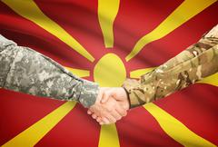 Stock Illustration of Soldiers shaking hands with flag on background - Macedonia