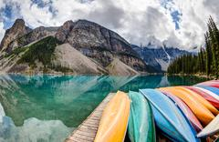Row of Kayaks on Moraine Lake in the Canadian Rockies - stock photo