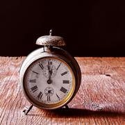 Old alarm clock on a rustic wooden table Stock Photos