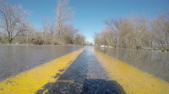 Water moving over flooded road view down double yellow lines Stock Footage