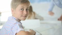 Portrait of schoolboy sitting in classroom - stock footage