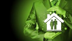 Businessman protecting family in home with hands Stock Photos