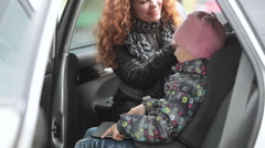 Mother preparing for the car trip, fastens kid with safety belt on booster chair Stock Footage