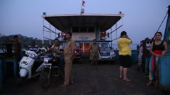 People and vehicles sailing on a ferry in Goa. Stock Footage