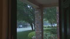 Woman peers through door at suburban rain shower Stock Footage