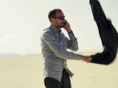Angry, lost businessman talking on cellphone standing on desert NTSC Stock Footage