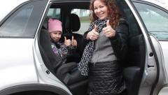 Caucasian mother and child showing thumbs up after seatbelt fastening in car - stock footage
