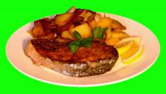4k fried potatoes with grilled fish and lemon on plate Stock Footage