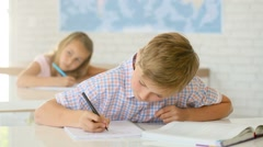 12-year-old boy in classroom writing on notebook Stock Footage