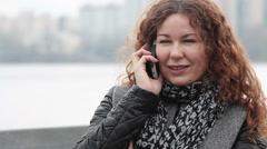 Happy smiling Caucasian woman calling on the cellphone while standing on city em Stock Footage