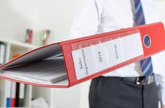 Businessman holding a red binder Stock Photos