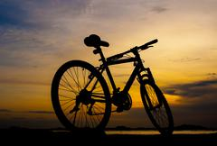 Silhouette of mountain bike parking on jetty beside sea with sunset sky backg Stock Photos