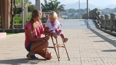 Blonde girl in Ukrainian blouse sits on child's chair outdoor Stock Footage