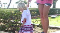 Blonde girl in Ukrainian walks along parapet taking mom's hand Stock Footage