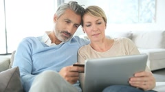 Cheerful mature couple e-shopping on internet Stock Footage