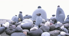 Tracking video shot of group of zen-like stone towers artistically arranged - stock footage
