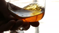 Swirling brandy in glass, slow motion CU Stock Footage
