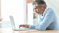 Mature man using laptop at home - stock footage