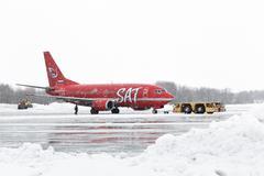 Airdrome trucks pulling Boeing 737-500 at airport of Petropavlovsk-Kamchatsky - stock photo