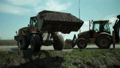 Excavator filling canal with gravel. Bulldozer spilling sand. Road construction. Stock Footage