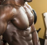 Attractive hunky black male bodybuilder pose in gym - stock photo