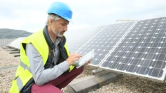 Mature engineer on building roof checking solar panels - stock footage