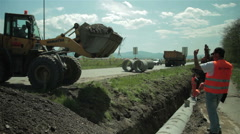 Heavy machinery at road construction, setting up sewage pipes, excavator,workers Stock Footage