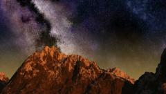 Time lapse of the sunrise from night sky with stars passing by behind mountain Arkistovideo