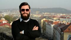 Young handsome man with full-beard (hipster) puts on his sunglasses and smiles Stock Footage