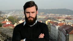 Young handsome man with full-beard (hipster) looks to camera (confident look) Stock Footage