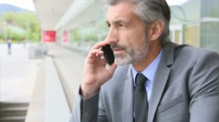 Mature businessman talking on phone outside building - stock footage