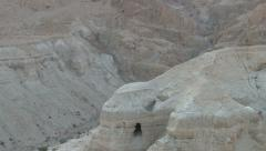 Qumran Caves - pan down from scroll cave on cliff to cave 4 Stock Footage