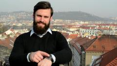 Young handsome man with full-beard (hipster) point to watch (time) - city Stock Footage