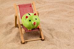 Deckchair with piggy bank Stock Photos
