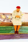senior sitting on banknotes - stock photo