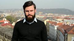 Young handsome man with full-beard (hipster) talks to camera and agrees - city Stock Footage