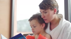 Slow motion of a young mother reading a tale to the son in the spa Stock Footage