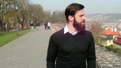 Young handsome man with full-beard (hipster) walking in park and looks on city Stock Footage