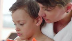 Young mother reading tale to kid in spa close up Stock Footage