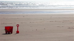 Beach bucket and spade with skipping children Stock Footage