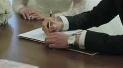 Bride and groom signing marriage certificate. Close-up - stock footage