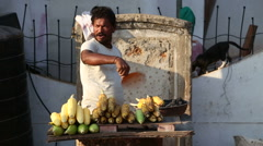 Indian man roasting corn at the street stand in Goa. Stock Footage