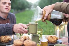 Group of people sitting round a table with food and drink, pouring coffee. Stock Photos