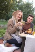Stock Photo of A couple sitting on the ground, food and drink on a table.