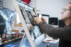 A man with a computer monitor, taking it apart to mend it. - stock photo