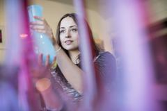Stock Photo of Woman holding a blue glass vase. Red and pink vases in the foreground.